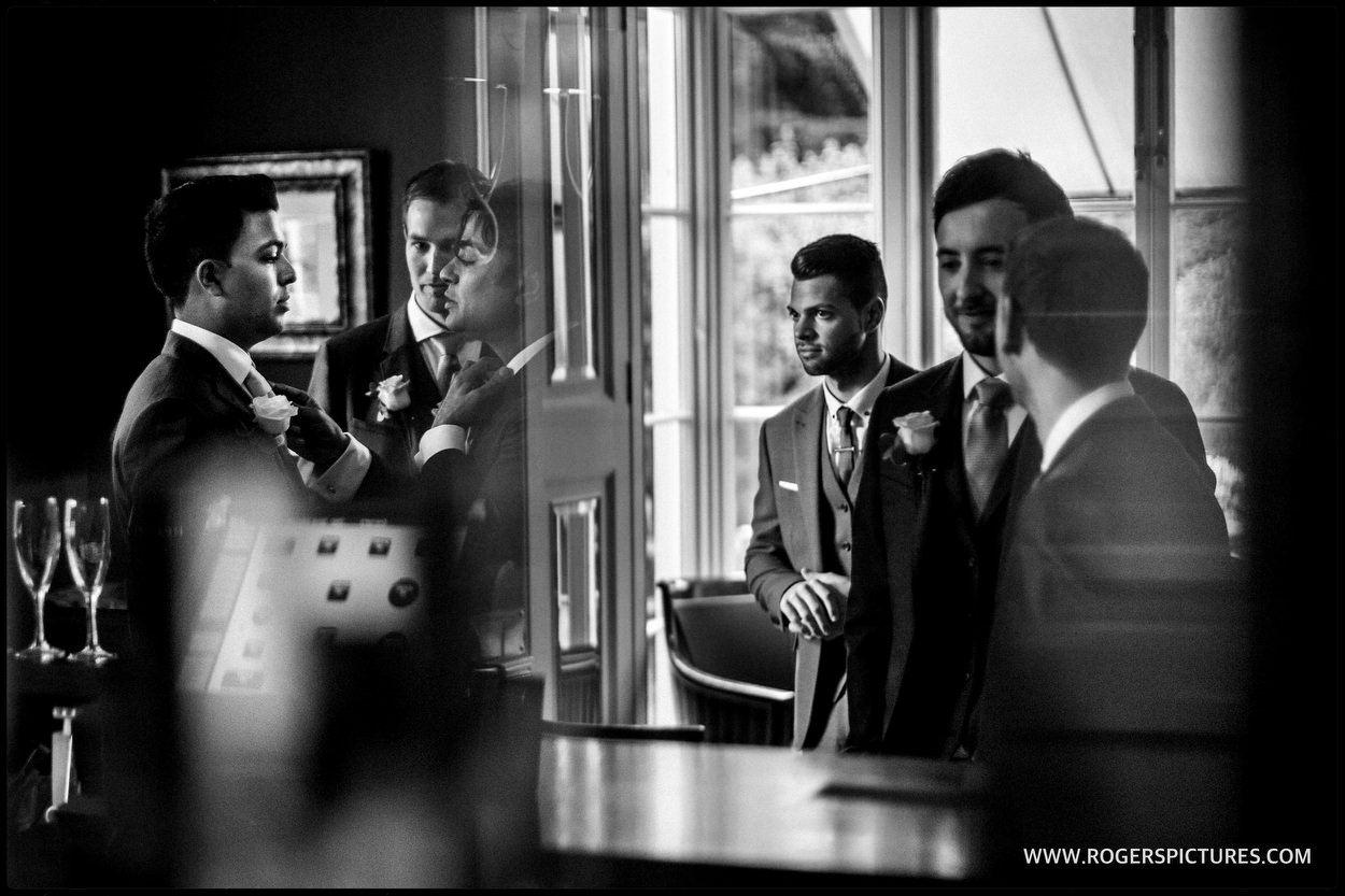 Documentary wedding photographer captures reflections of groomsmen in the bar before a wedding ceremony