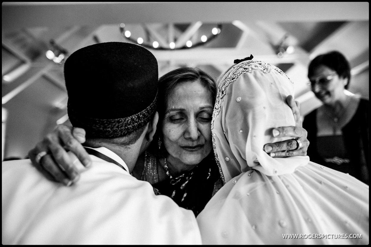 Guest hugs bride and groom at zoroastrian wedding