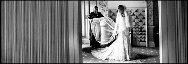 Black and white photo of a bride in her wedding dress framed in a doorway