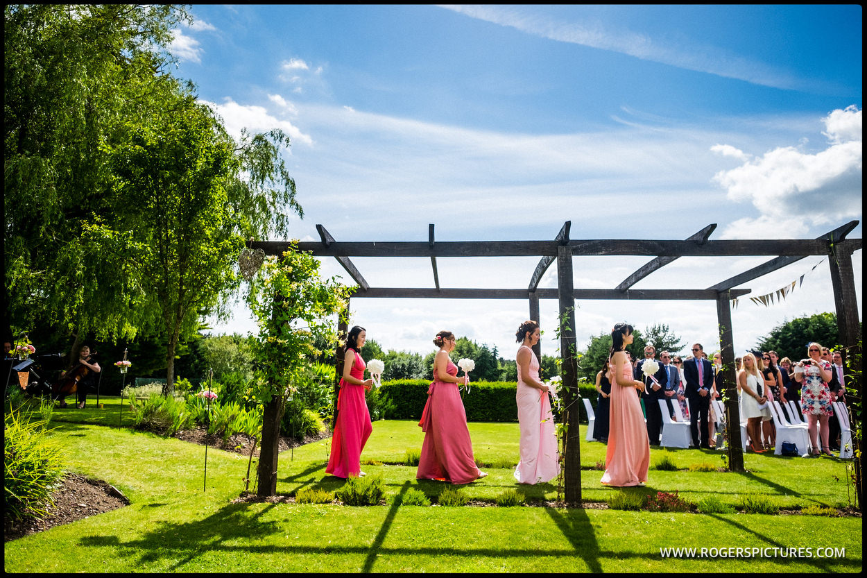 Bridesmaids at an outdoor wedding ceremony in the gardens at Cain Manor