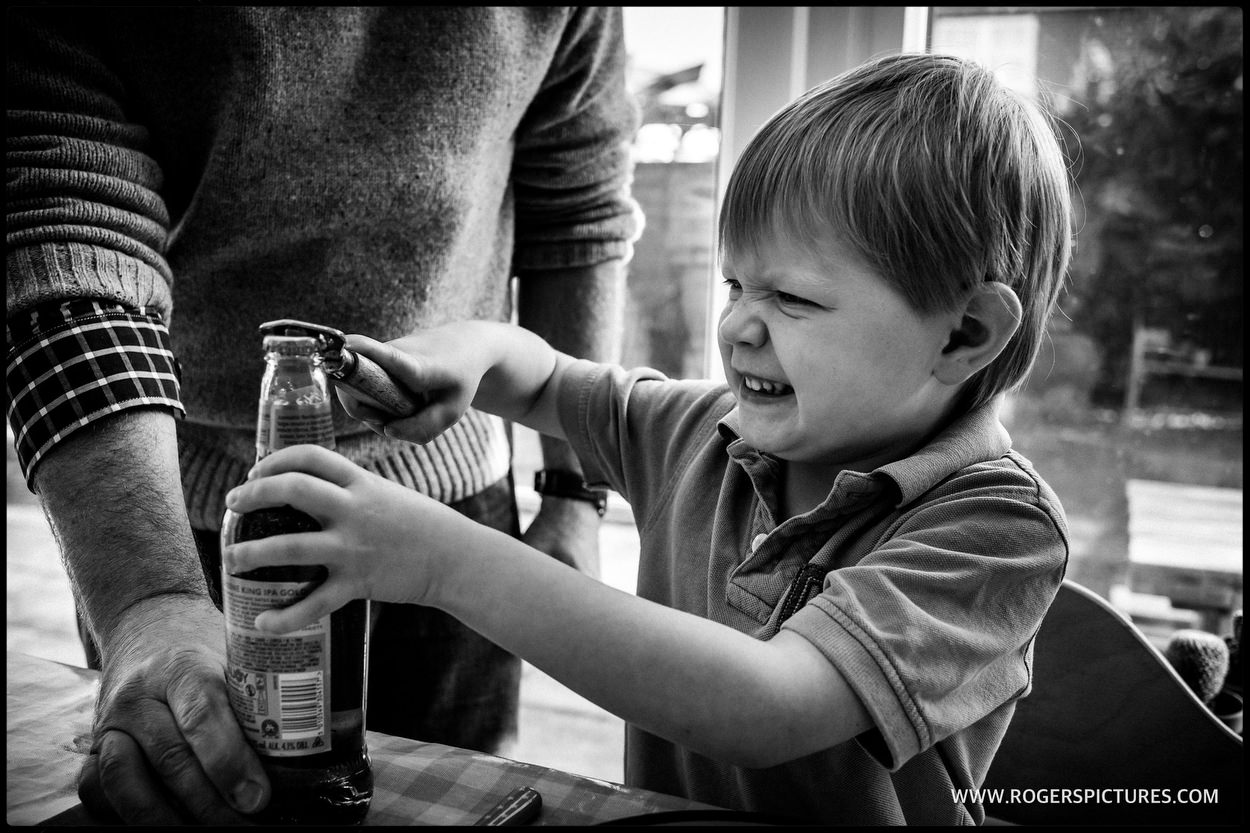 Little boy opening a beer bottle for his dad