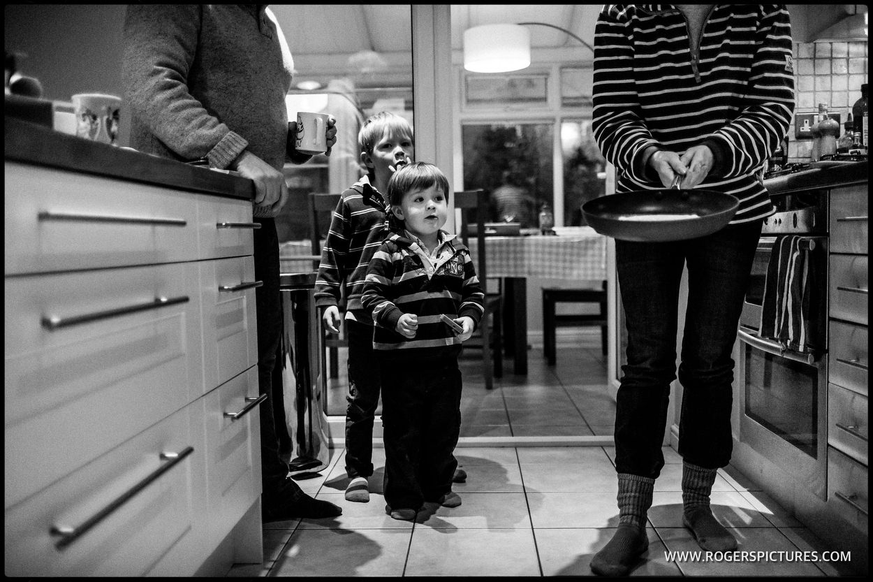 Boys watch mum flip a pancake