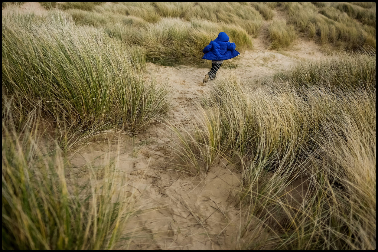 Boy running through dunes