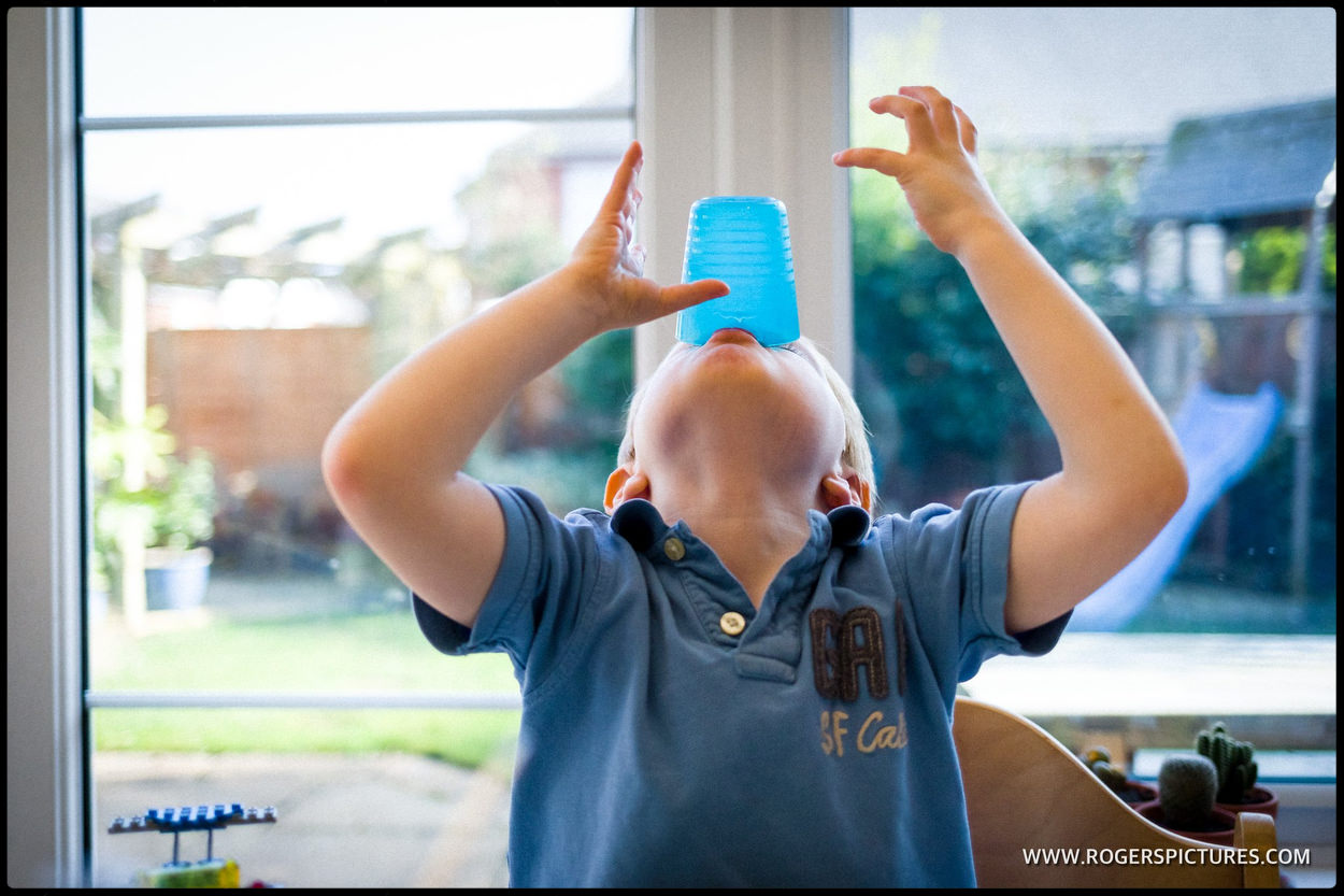 young boy drinks from blue cup