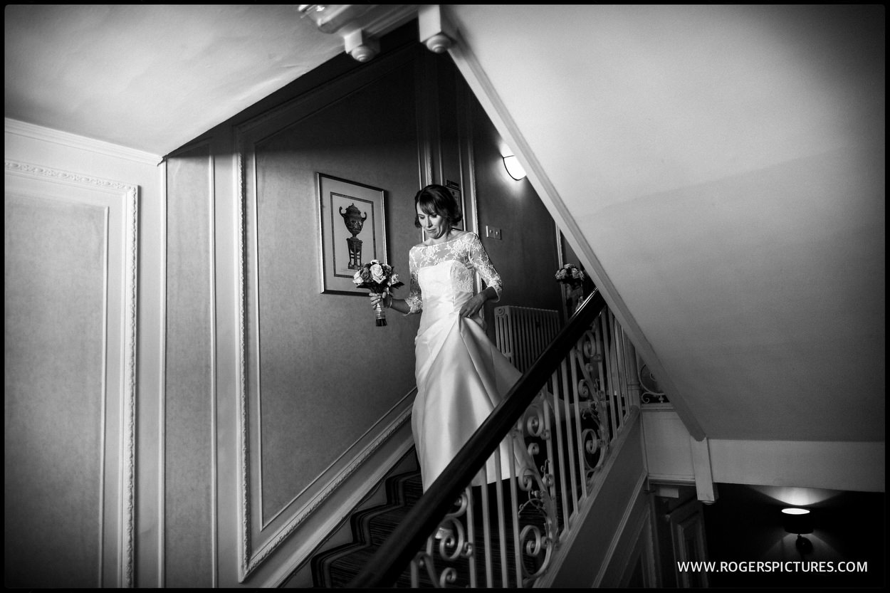 Bride walking down the stairs at Gorse Hill in Surrey