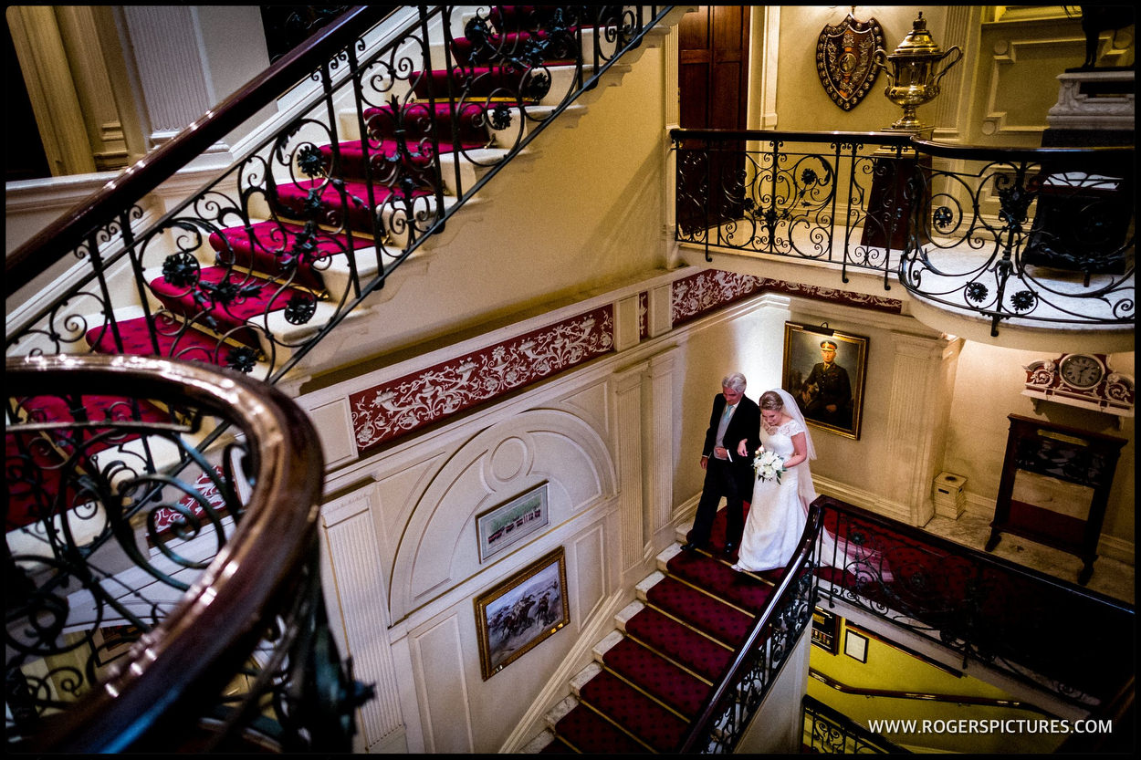 Bride and father walk down the stairs before a wedding