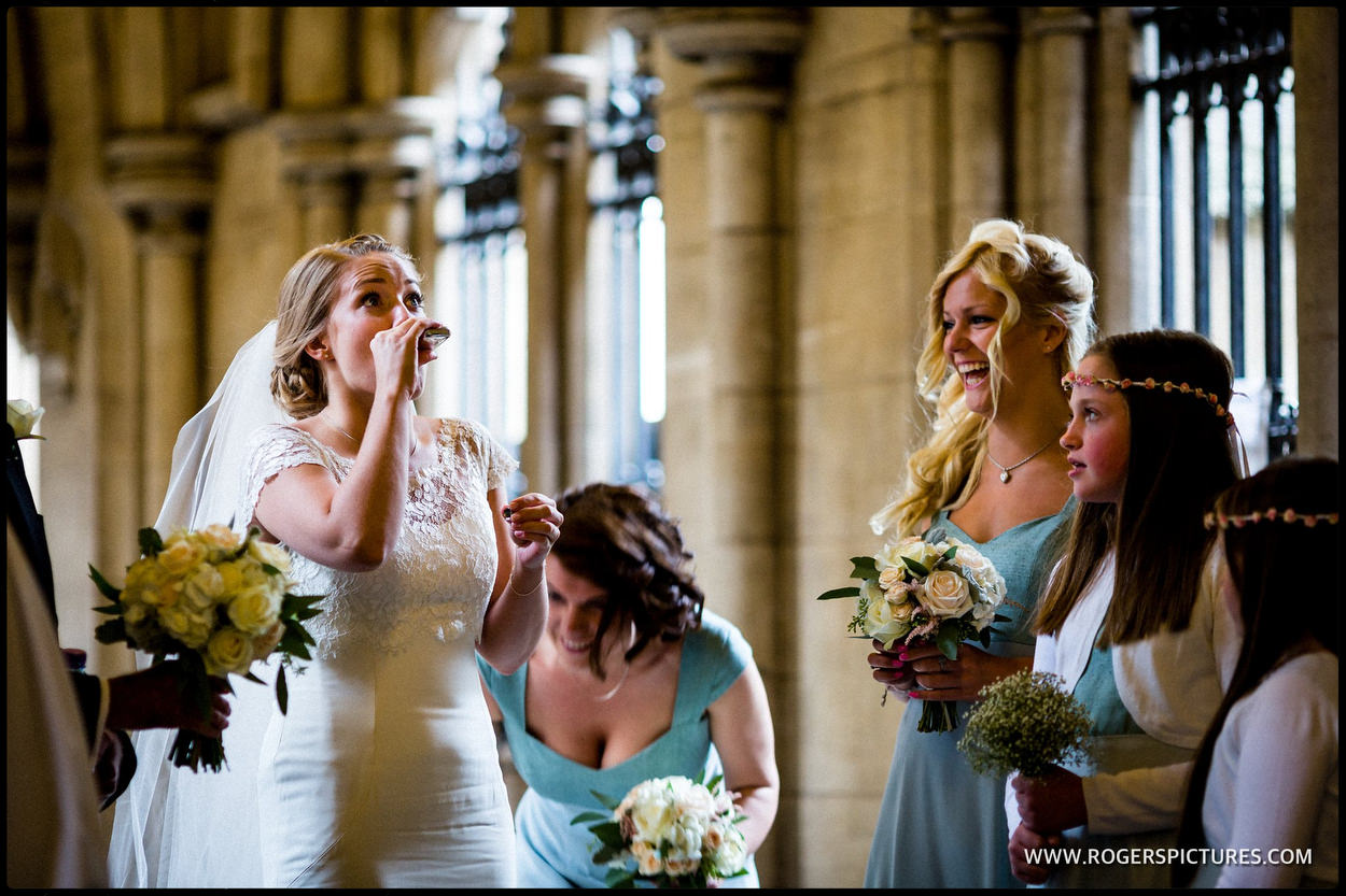 Bride takes a quick drink before a church wedding in London