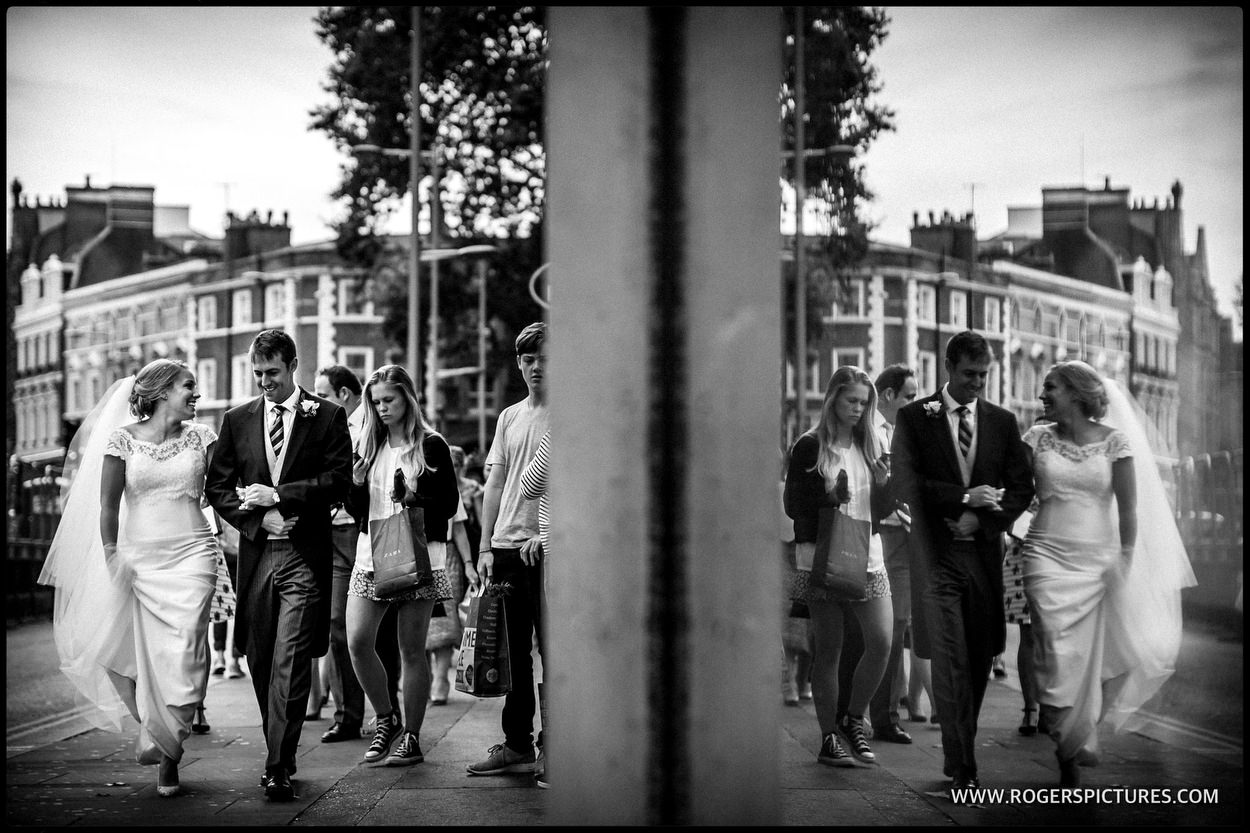 Kensington wedding couple walk through the High Street
