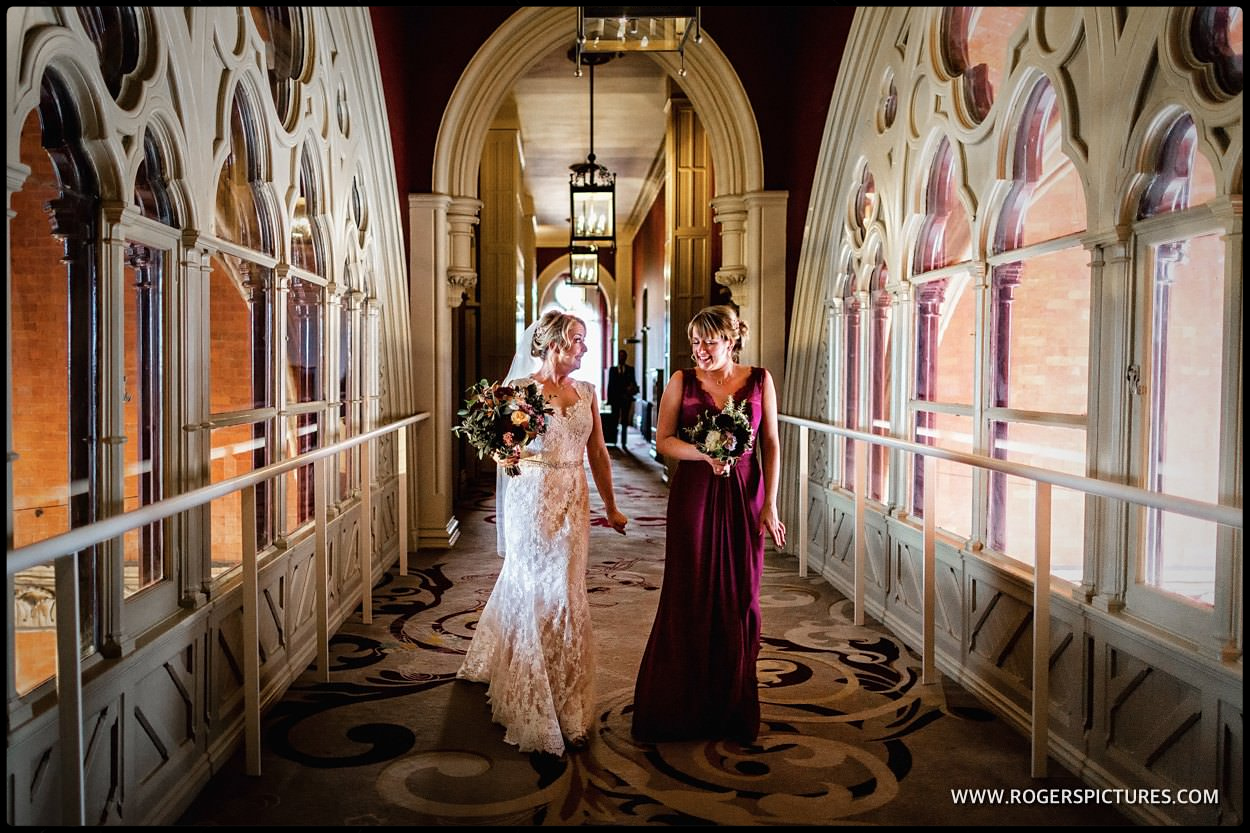 Bride and sister walk along the corridor at St Pancras Hotel