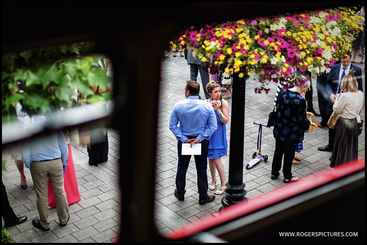 Wedding guests framed in a double-decker bus window