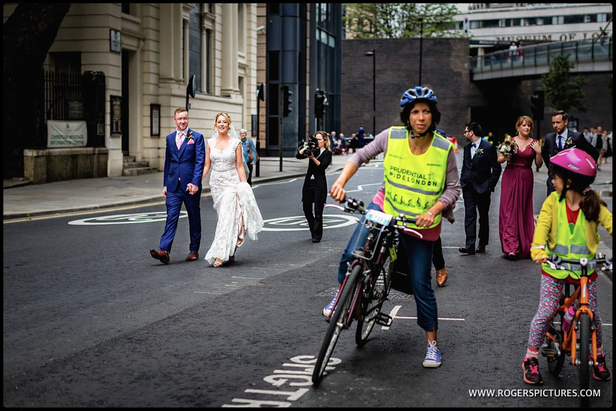 Bride and groom walk through London with cyclists