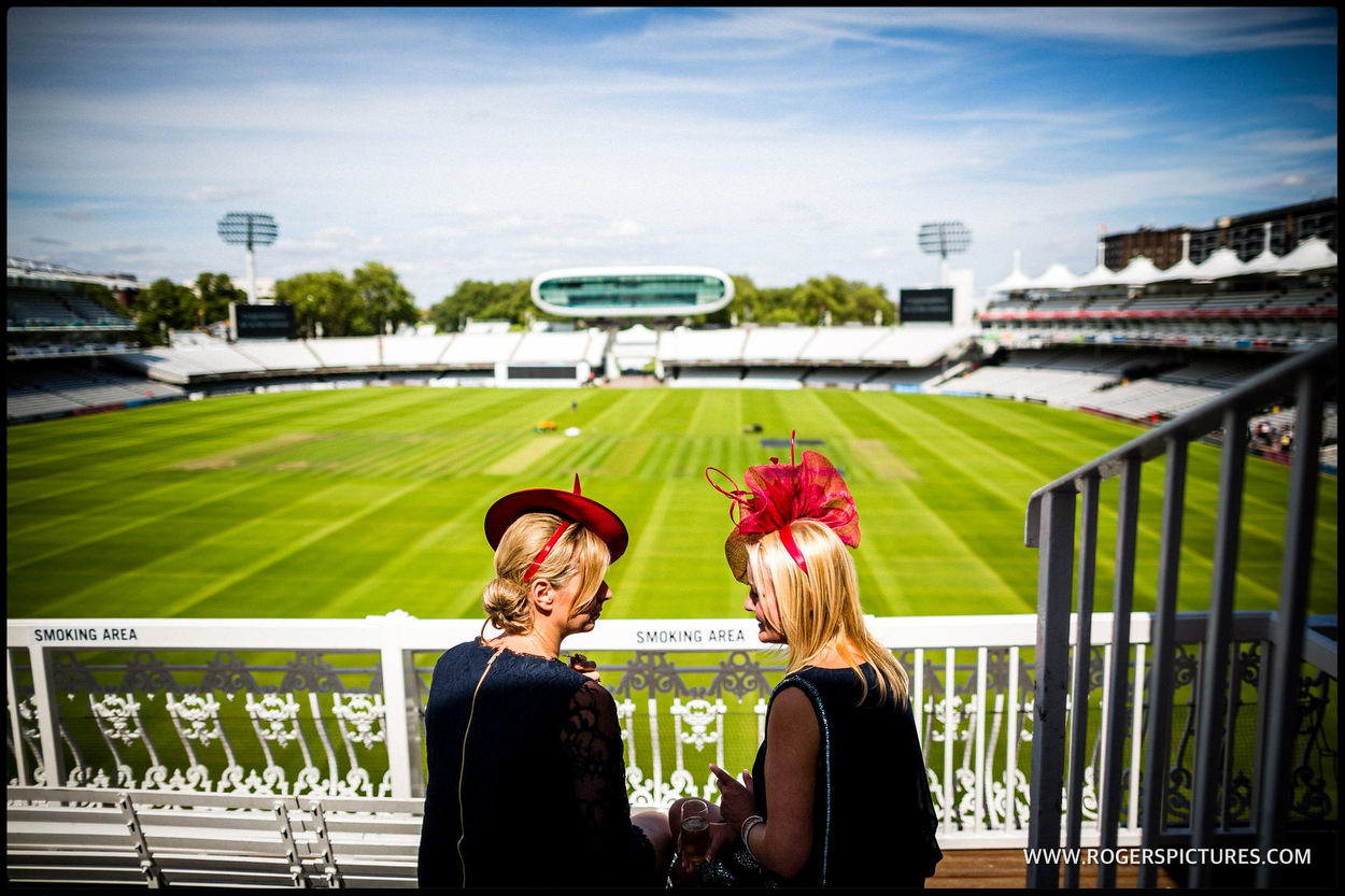 Wedding guests in red hats at Lords Cricket Ground