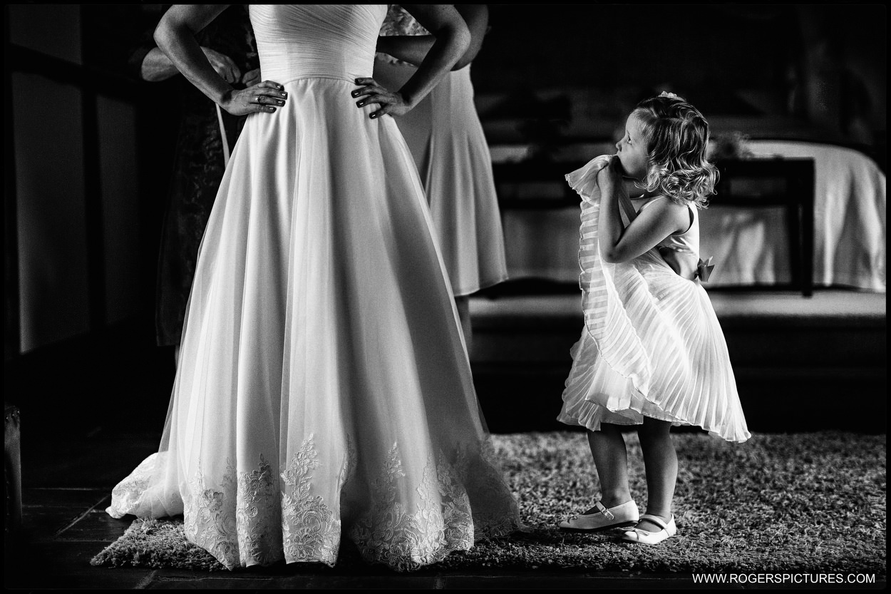 Black-and-white photograph of flower girl looking at brides getting dressed