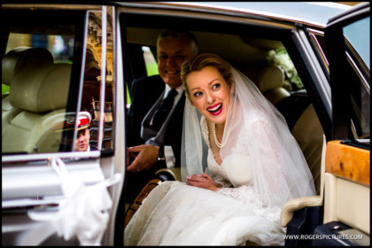Beautiful and smiling bride arrives in a Rolls Royce