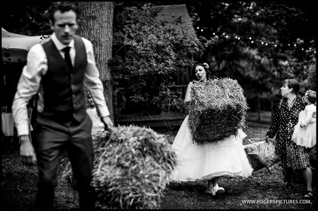 Bride and groom moving hay bales