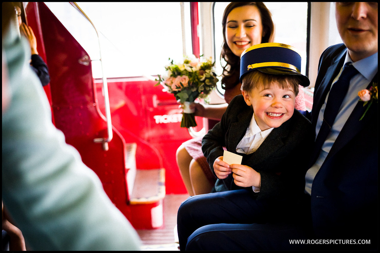 Boy in bus bus conductors hat on a wedding bus