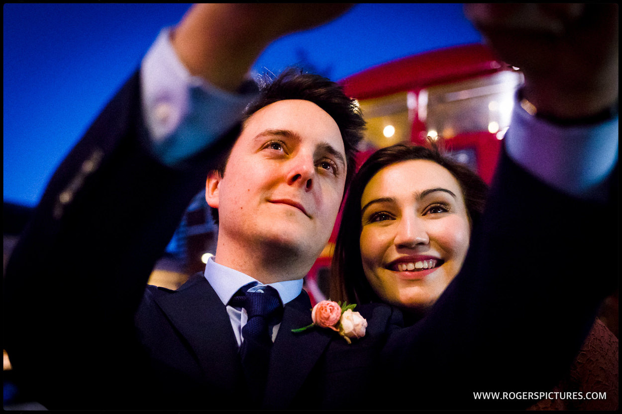 Bride and groom selfie in front of London wedding bus