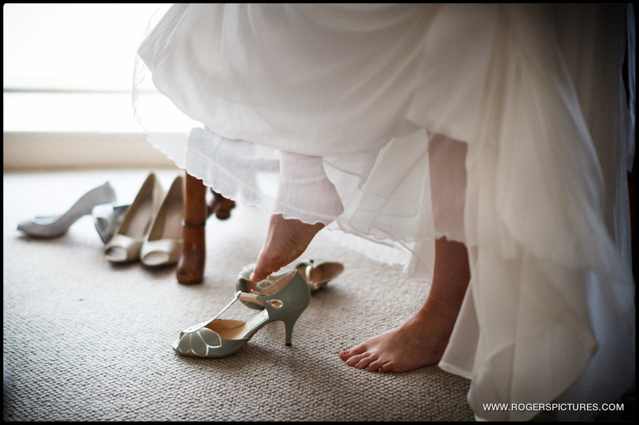 Bride in white dress steps into her wedding shoes