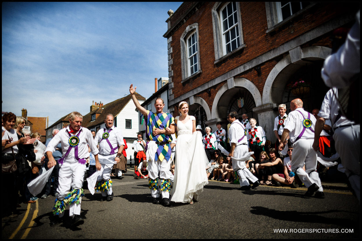 The Fool with a bride surrounded by Morris Dancers at a sunny wedding