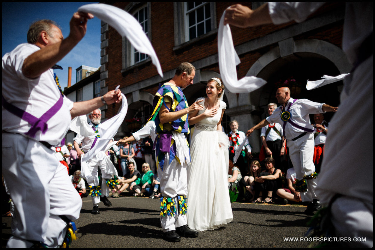 Bride dancing with Morris dancers waving handkerchiefs