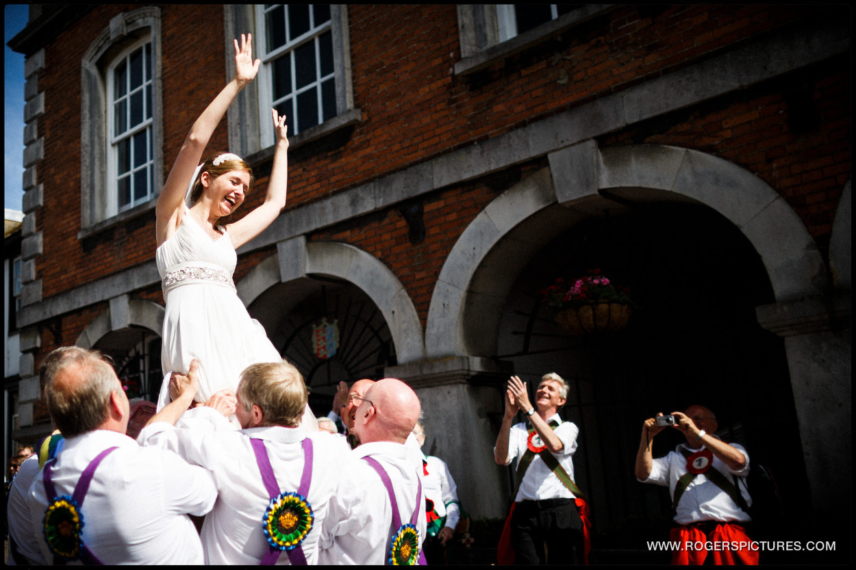 Laughing bride lifted into the air by Morris Dancers