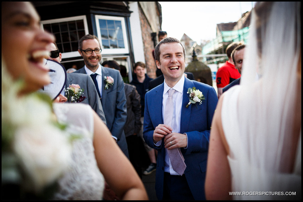 Groom laughs with Morris Dancers after they danced with his wife
