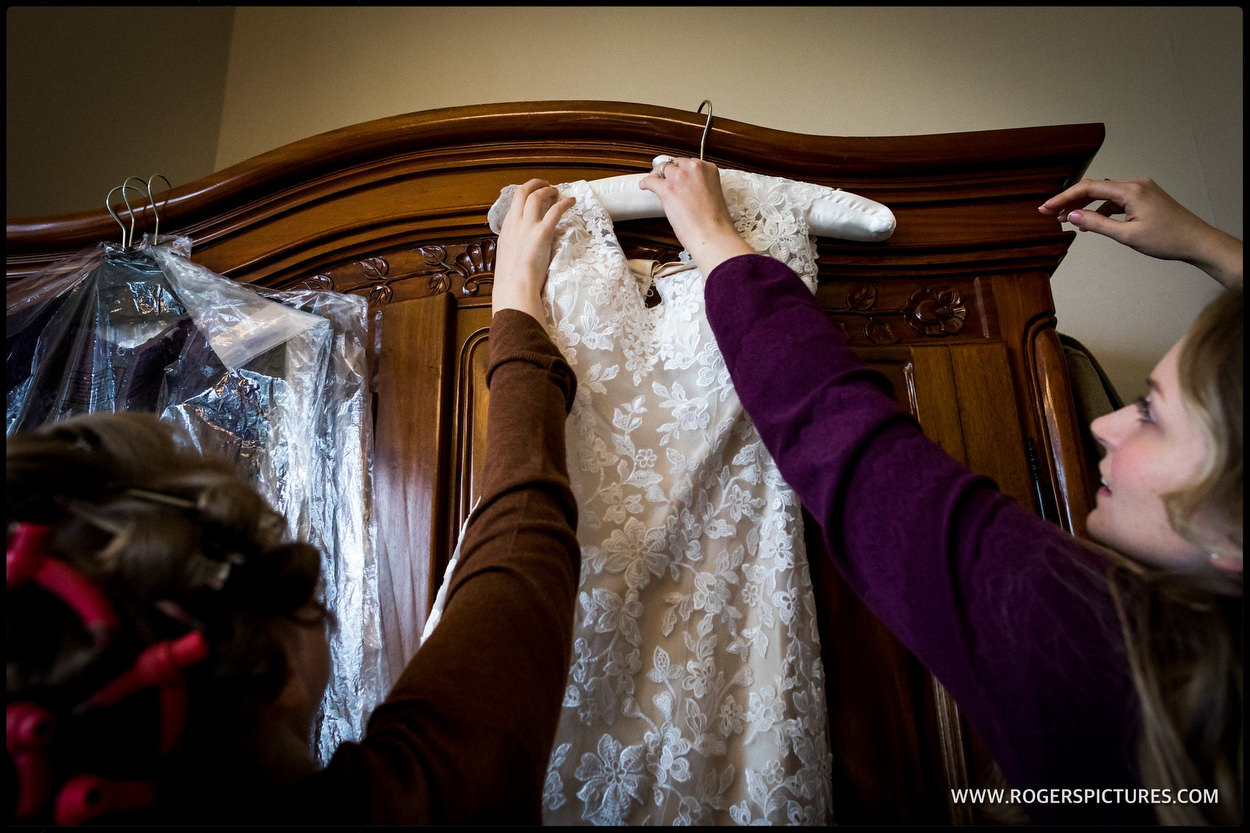 Bridesmaids hang a wedding dress at Orchardleigh House