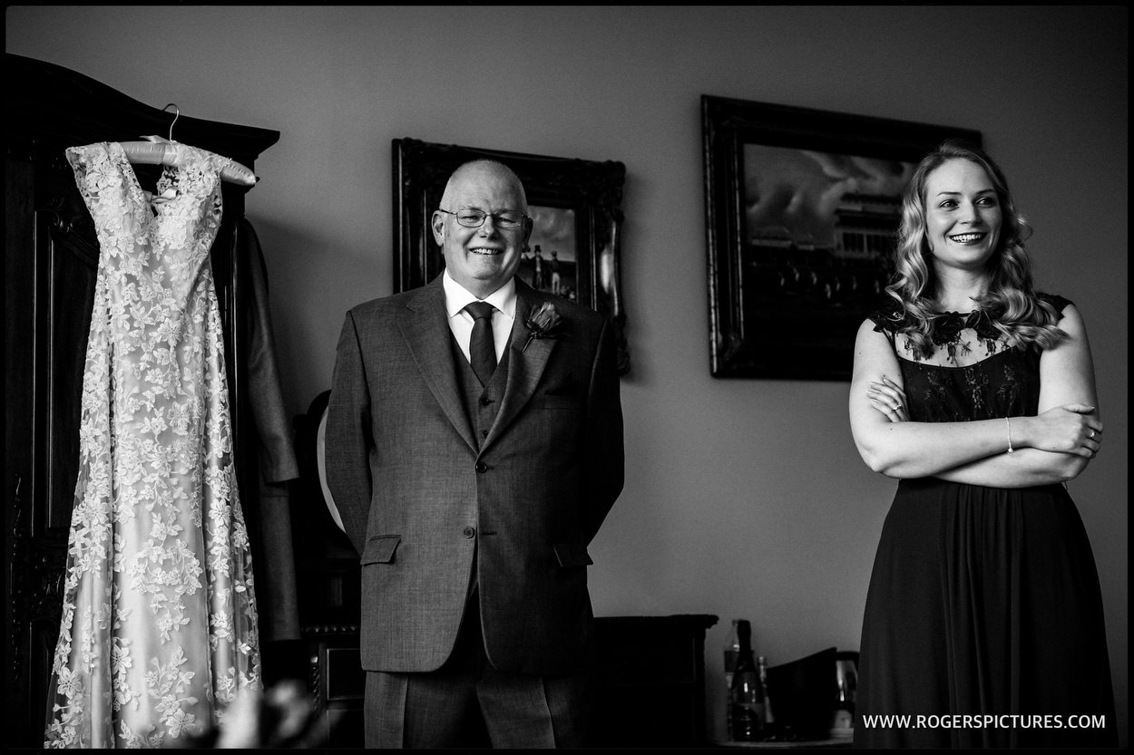 Bridesmaid and father of the bride with wedding dress