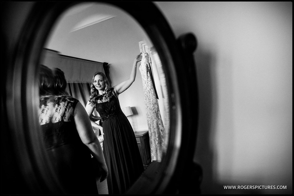 Bridesmaid reflected in an oval mirror