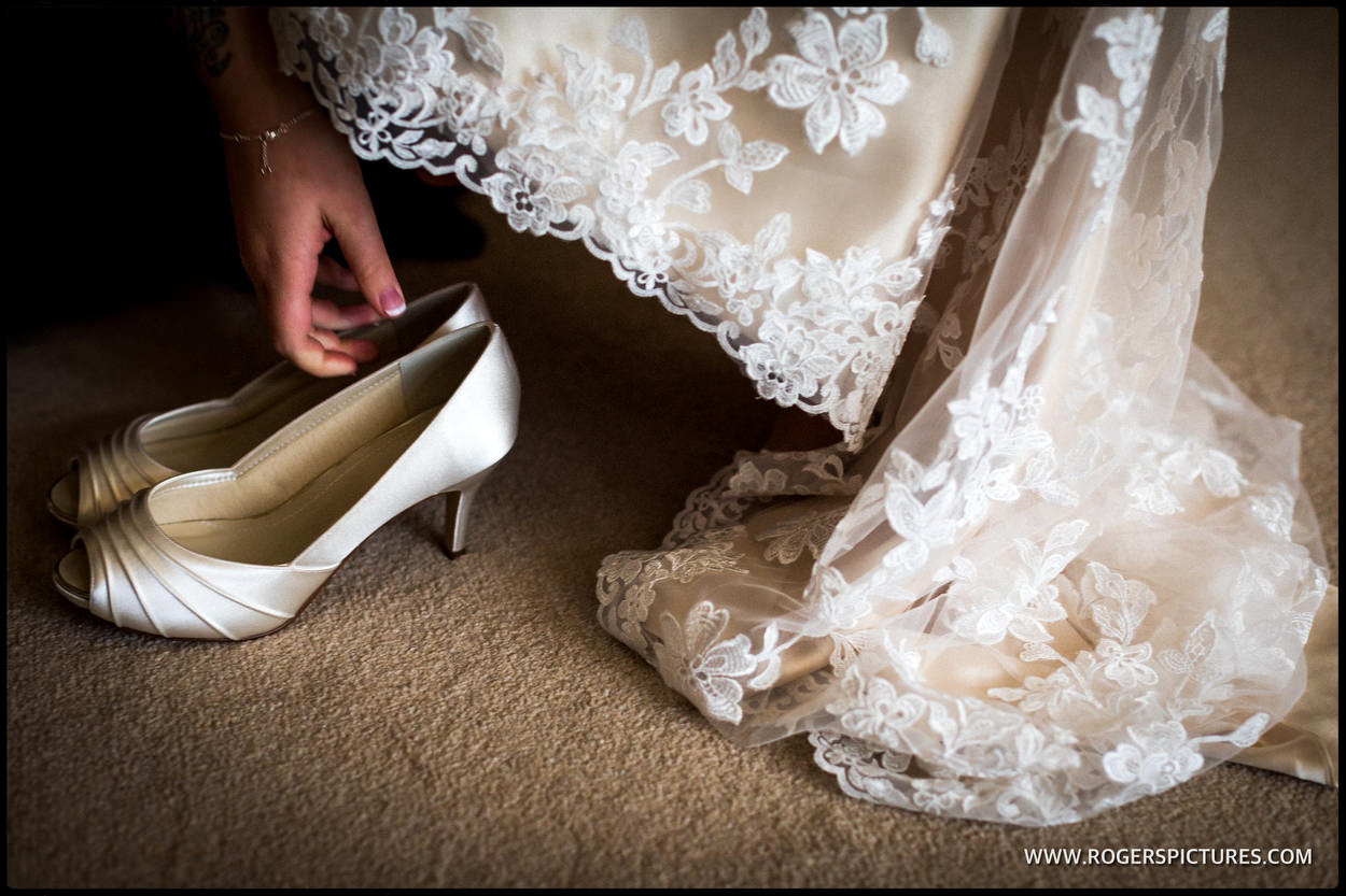 Detail photograph of a brides shoes and lacy dress
