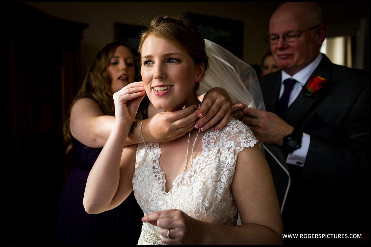 Father of the bride helps his daughter get ready for wedding