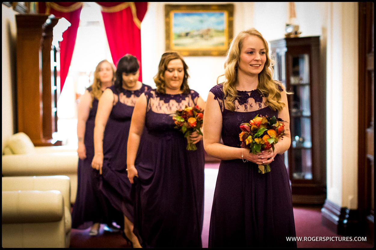 Bridesmaids in purple dresses walk down the aisle at Orchardleigh House
