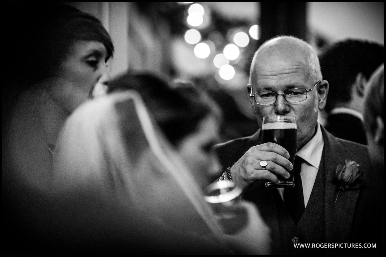 Wedding guest sips a pint of beer