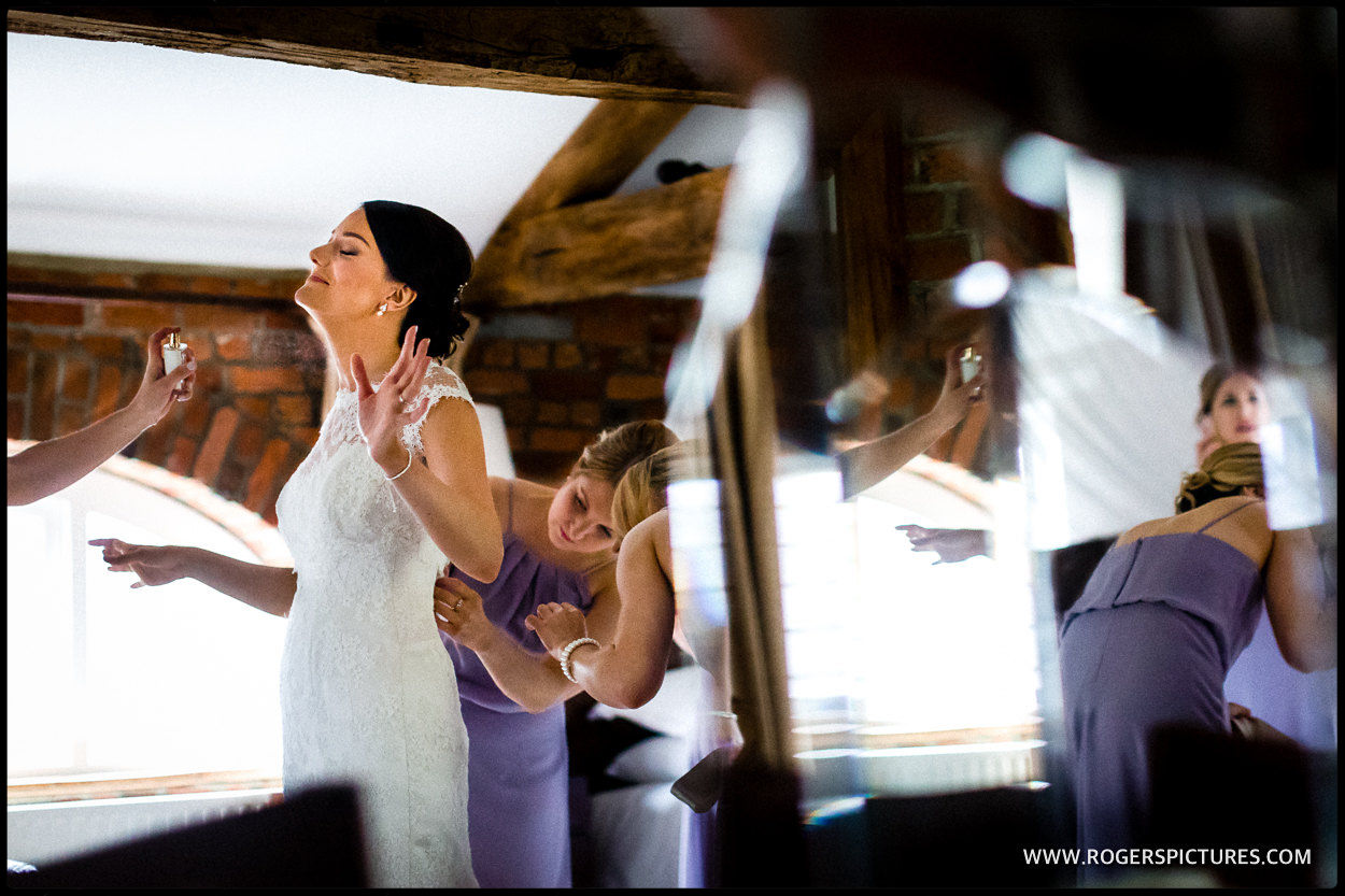 Perfume being sprayed onto a bride on the morning of her wedding