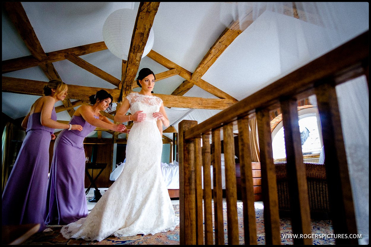 Bridesmaids in purple dresses assist bride