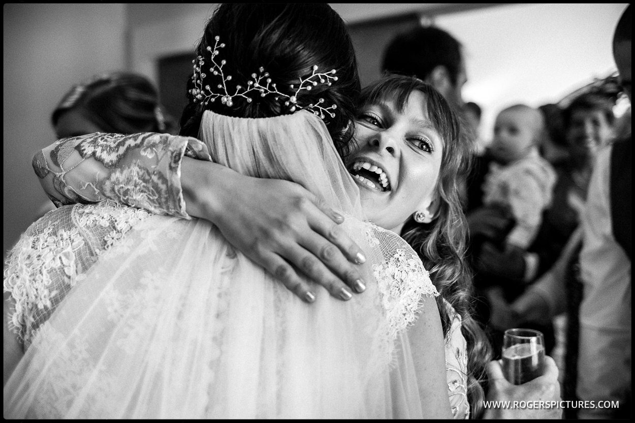 Documentary photography of guest hugging a bride