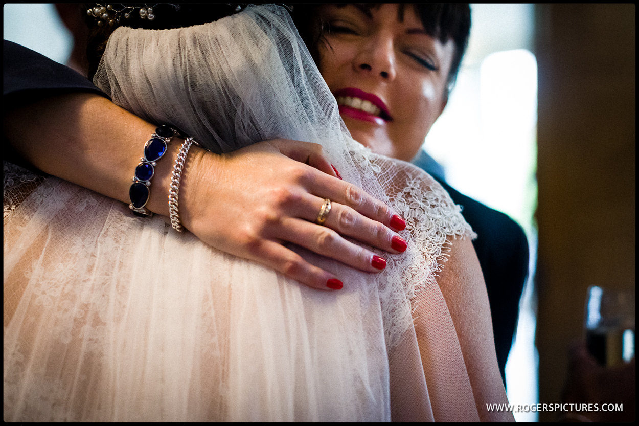 Lady with red nail varnish hugs a bride