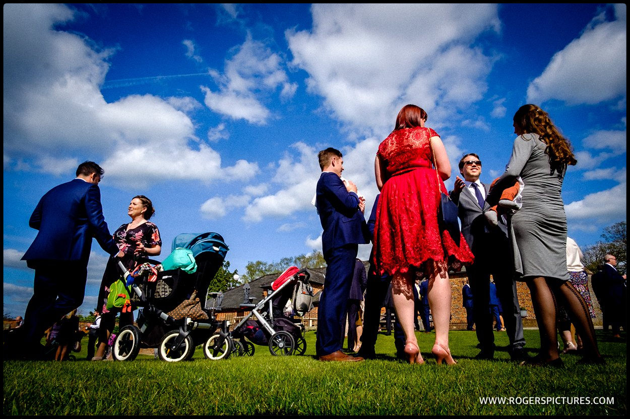 Colour photo of wedding guests in the sunshine