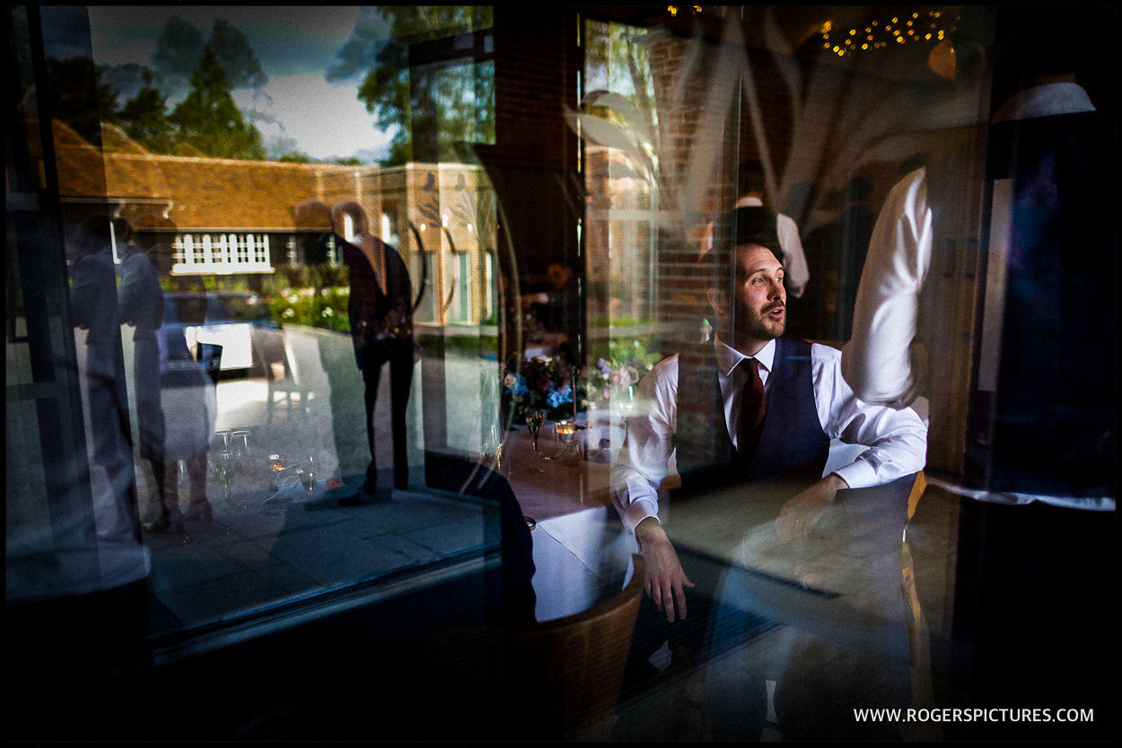 Groom through a window reflection
