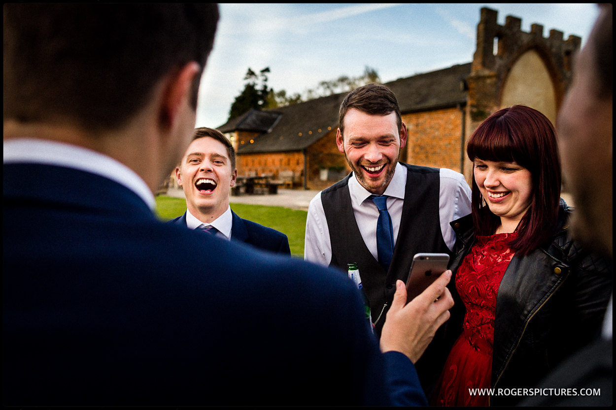 Guests laugh at a phone