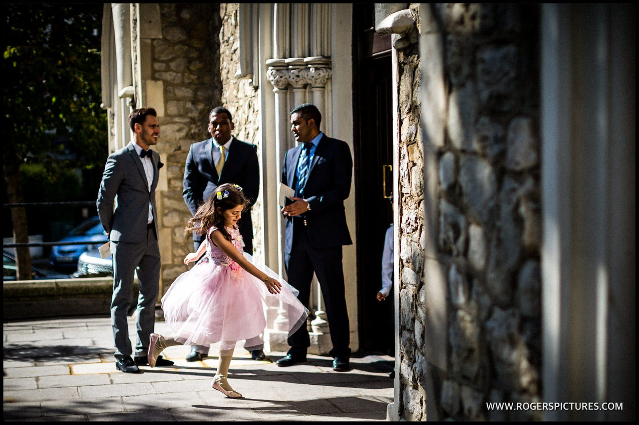 Backlit flower girl at a church wedding