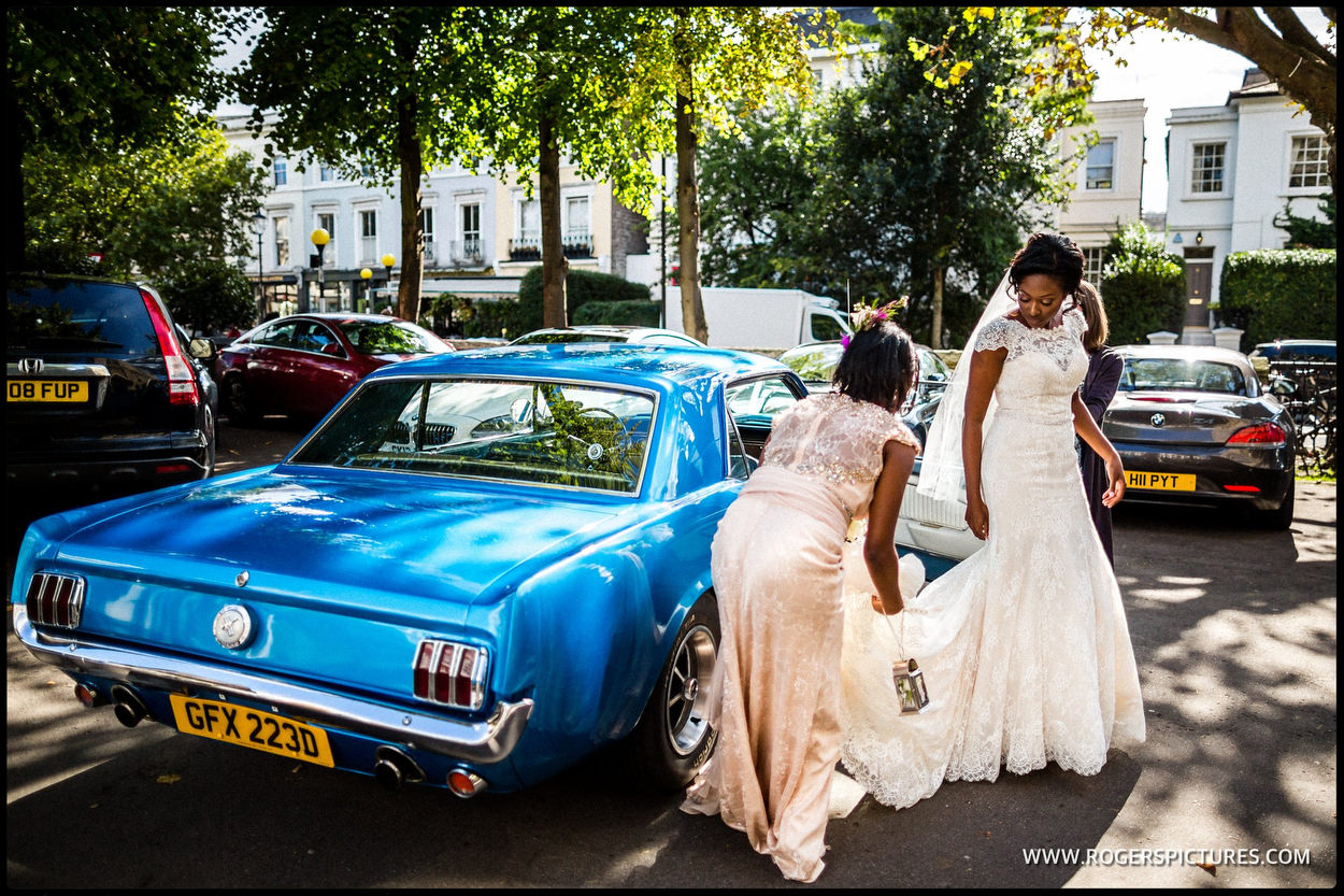 Bride stepping out of a blue Mustang