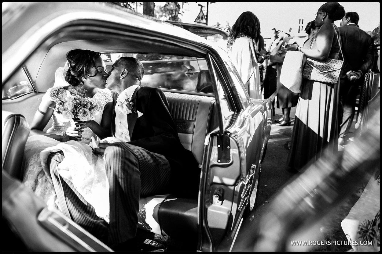 Bride and groom kiss in wedding car