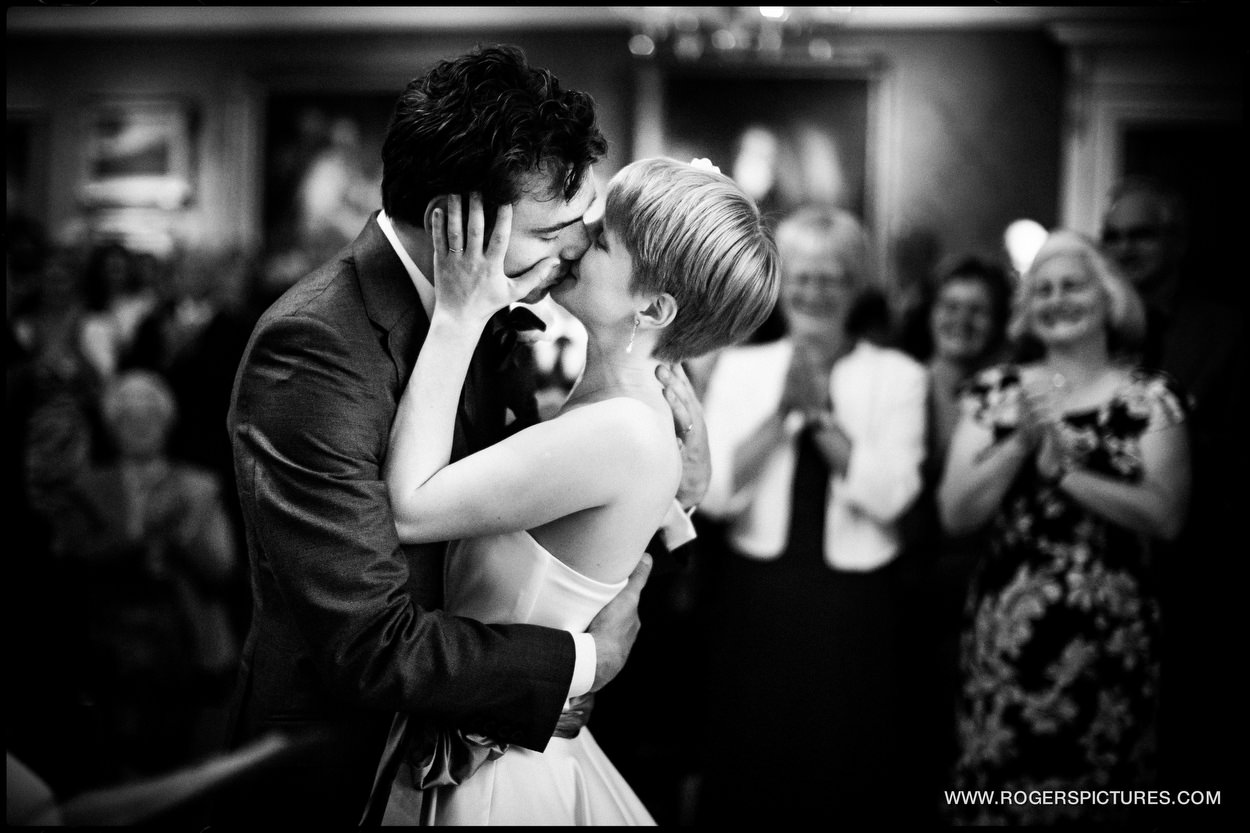 Documentary wedding photograph of couple kissing after marrying