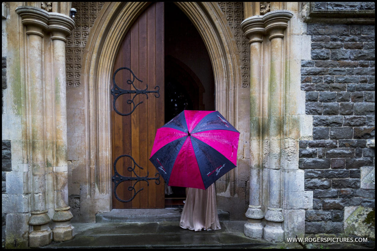 Black and red umbrella at a church door before wedding
