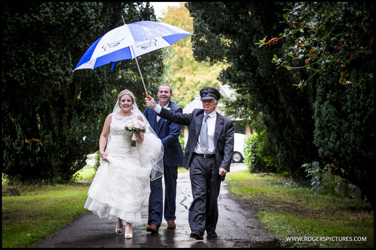 Bride with umbrella walking to Church