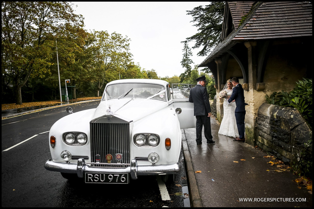 Bride and groom get into a Rolls-Royce wedding car
