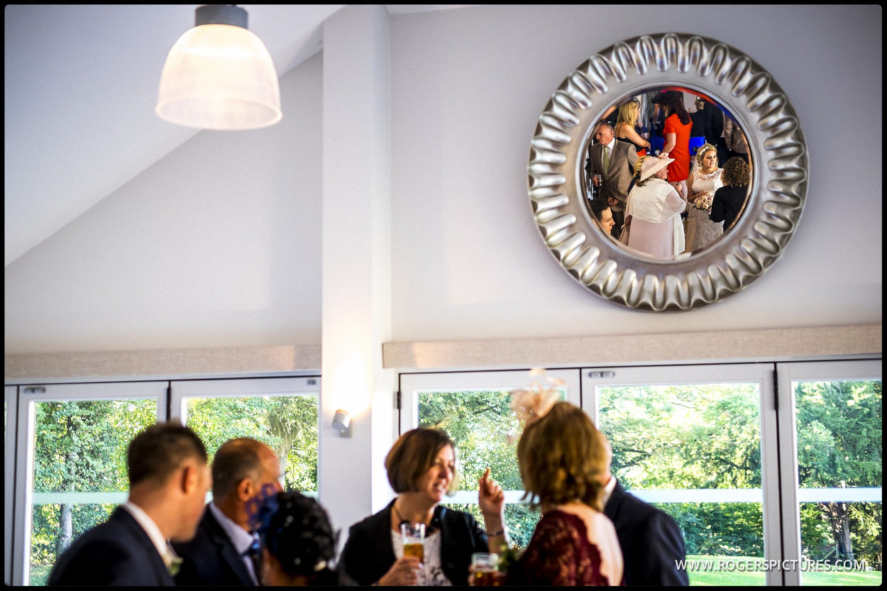 Wedding guests reflected in circular mirror