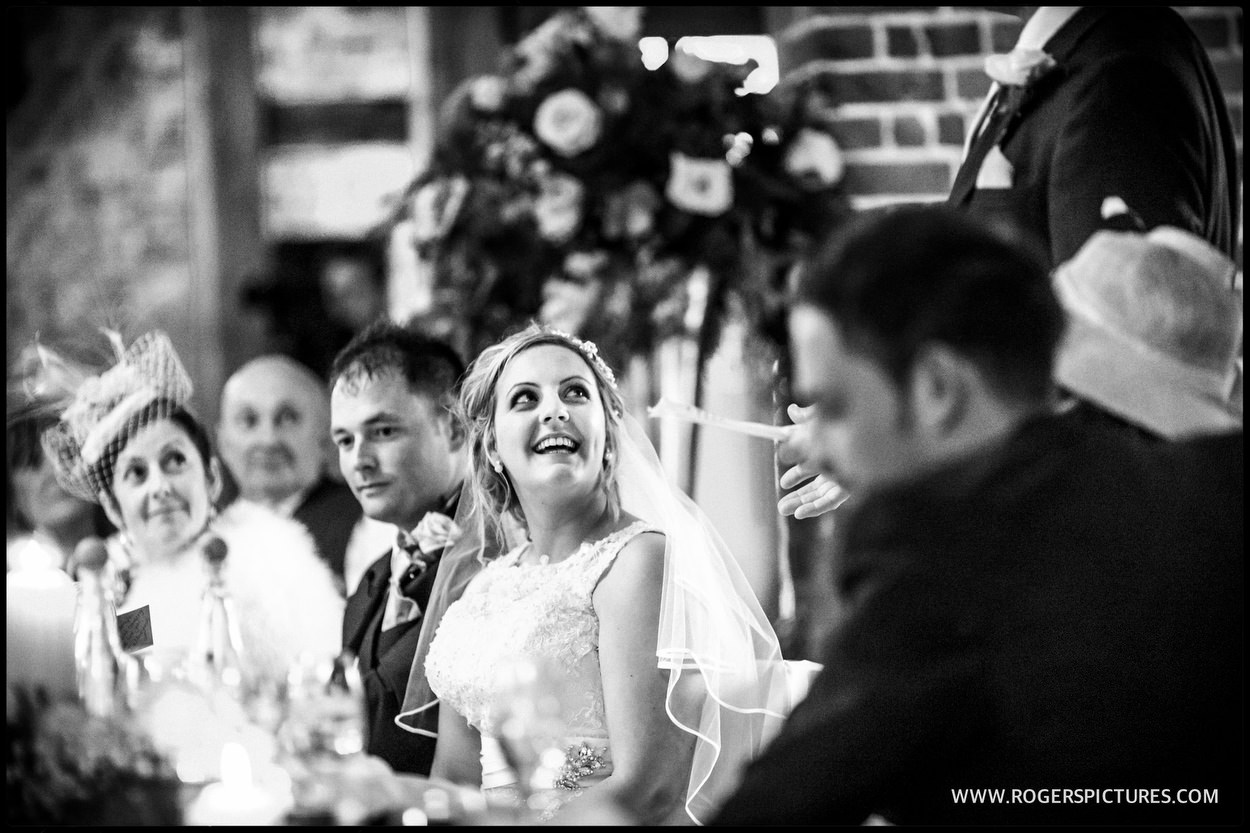 Bride listens to speeches in a barn