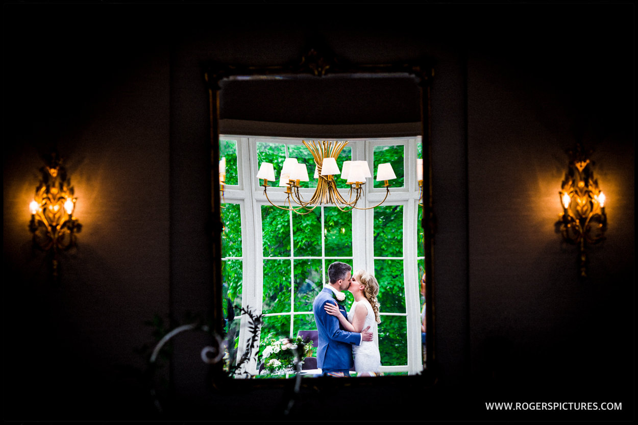 Reflection of bride and groom kissing after wedding ceremony